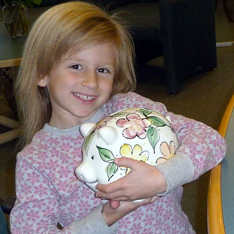 alex holding her hand-made ceramic piggy bank